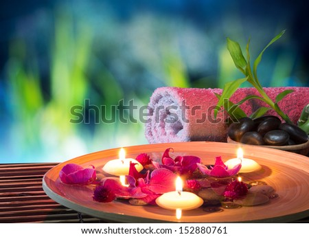 dish spa with floating candles, orchid, bambu towel in garden - stock photo