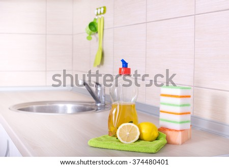 Dish washing concept. Close up of lemon, detergent in bottle and sponges for dishwashing on the kitchen countertop - stock photo
