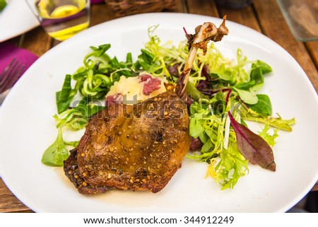 Dish with a roasted duck leg and green salad on a white plate