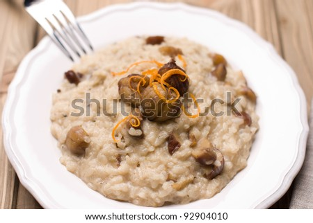 Dish with chestnut risotto with blue cheese on a wooden background - stock photo