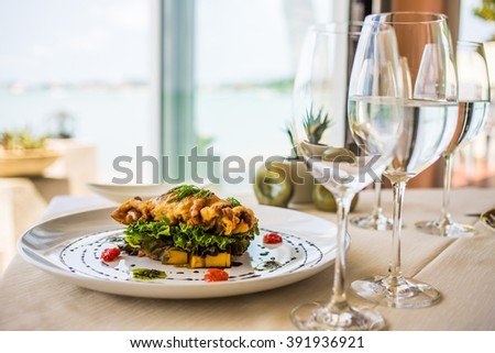 dish with cooked crab, glass of water, beach restaurant serving, sea view - stock photo