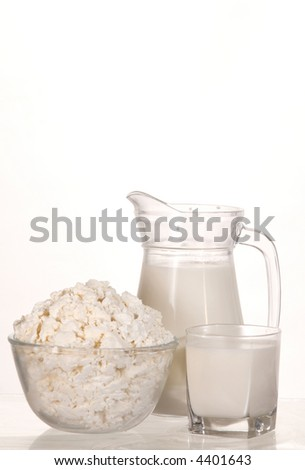 dish with cottage cheese and glass with milk