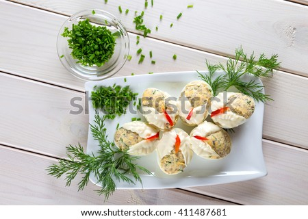 Dish with hard boiled eggs in mayonnaise parsley nad chopped chives, on white plank background - stock photo