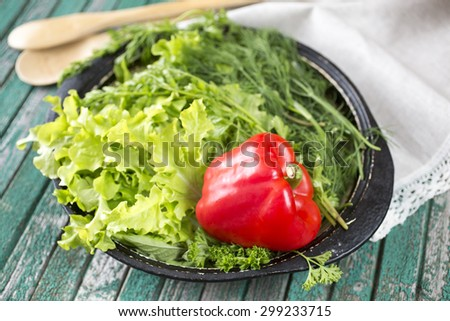 Dish with pepper and green-stuff on a wooden table