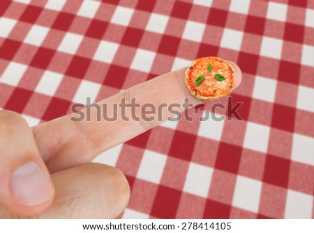 Dish with Pizza margherita in miniature on the finger with tablecloth with red checkered pattern. - stock photo