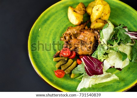 Dish with quail, fried potatoes and vegetables on green plate. Top view