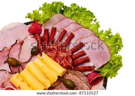 Dish with sliced ham, cheese, salami rolls and lettuce closeup view. - stock photo