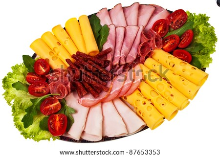 Dish with sliced ham, cheese, salami rolls, bacon and lettuce over white background. - stock photo
