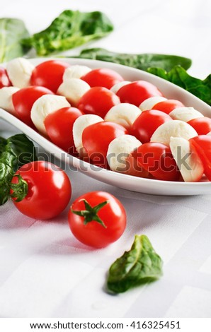 dish with sliced mozzarella cheese balls and ripe cherry tomatoes in caprese salad on the white table. vertical format - stock photo
