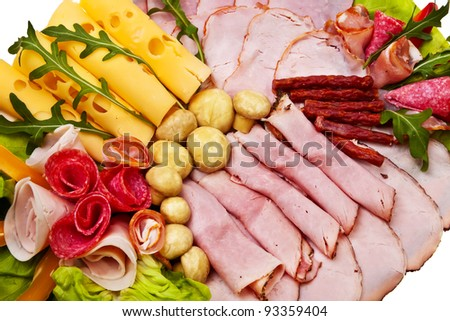 Dish with sliced smoked ham, salami rolls and cheese over white background.