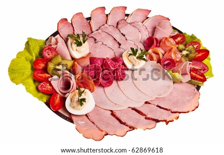 Dish with sliced smoked ham, salami rolls, boiled eggs, cherry tomatoes over white background. - stock photo