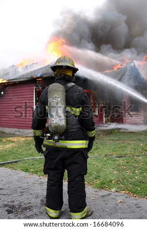 Disheartened fireman in front of a burning house - stock photo