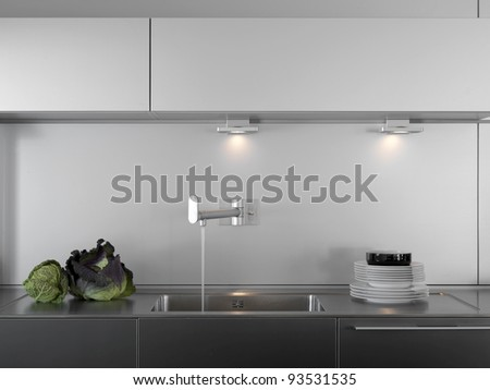 dishes and vegetables on the steel top and water tap in a modern kitchen - stock photo