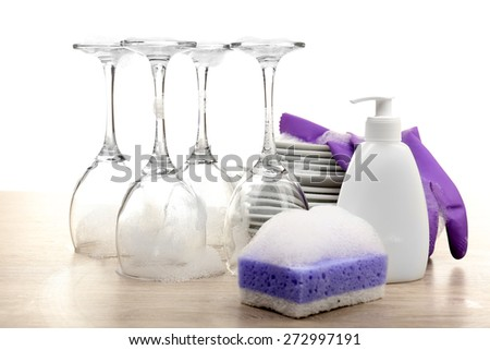 Dishes in foam with gloves and wisp on table isolated on white - stock photo