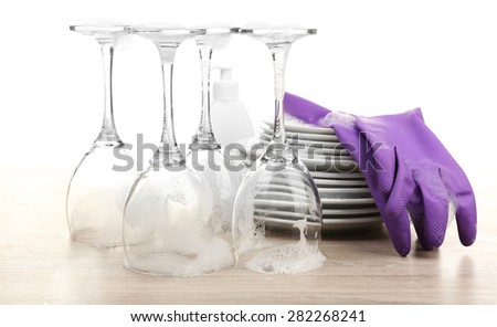 Dishes in foam with gloves on table isolated on white - stock photo