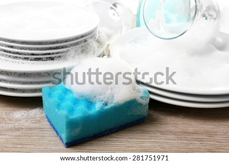 Dishes in foam with wisp on table close up - stock photo