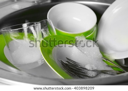 Dishes in kitchen sink closeup - stock photo