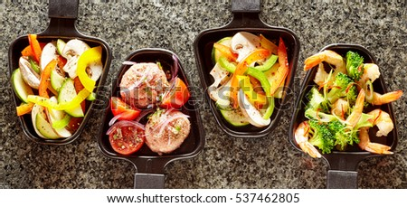 Dishes of assorted ingredients to be added to raclette cheese with sliced bell peppers and mushrooms, meatballs, tomato, shrimp tails with broccoli in individual skillets on a granite kitchen counter