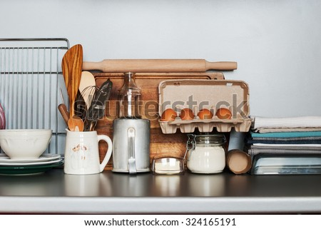 Dishes, Tableware and Fresh Grocery Products stand on a Kitchen Table - stock photo