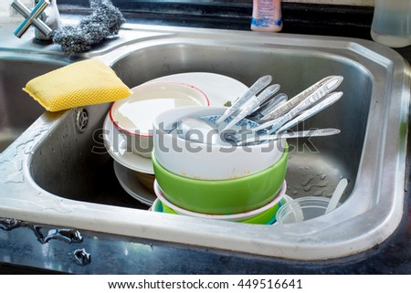 Dishes wait for washing in kitchen sink