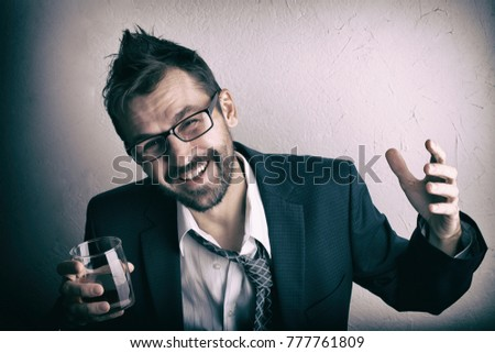 Disheveled bearded man in suit with a glass of whiskey