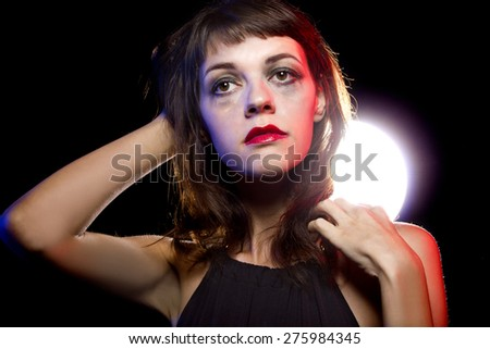 Disheveled drunk or female high on drugs at a nightclub.  She is alone like an outcast.  Lit with red and blue color gels for nightclub effect. She is alone like an outcast.