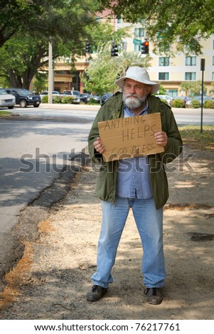 Disheveled homeless man stands by the side of the road begging for help by holding a sign. - stock photo