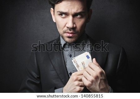 dishonest man puts money in the jacket - stock photo