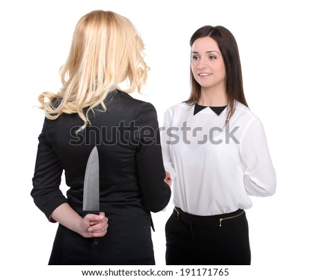 Dishonest partnership. Two young business woman shaking hands and holding knifes behind their backs. - stock photo