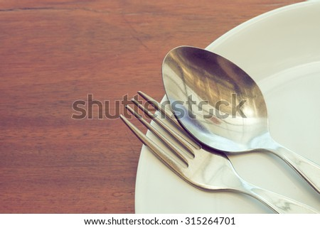 dishware set on wood table with plate, spoon and fork, image used filter vintage