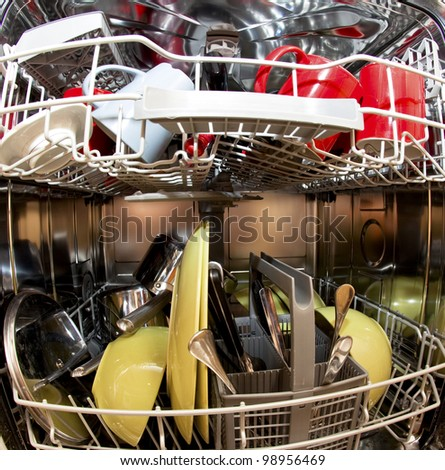 Dishwasher with dirty dishes in kitchen - stock photo