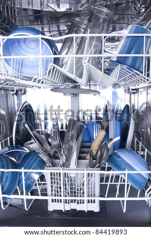 Dishwasher with knives forks and blue plates - stock photo