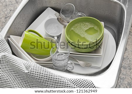 Dishwashing. Bright dishes in the sink and kitchen towel. - stock photo