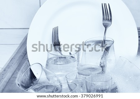 Dishwashing - Glassware,cutlery and dishes in the kitchen sink - stock photo