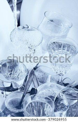 Dishwashing - Glassware,cutlery and dishes under a water jet in the kitchen sink - stock photo