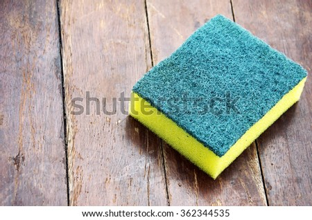 Dishwashing sponge with a wooden floor in the background. - stock photo