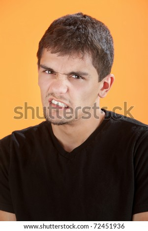 Disinterested Mexican American guy on an orange background - stock photo