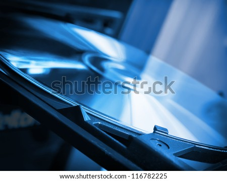 Disk in dvd-rom in blue colors - stock photo