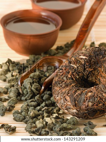 disk Puer tea and green tea leaves - stock photo