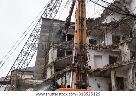 Dismantling of a house. Building demolition and crashing by machinery for new construction. - stock photo