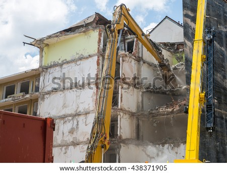 Dismantling of Building crashing by machinery - stock photo