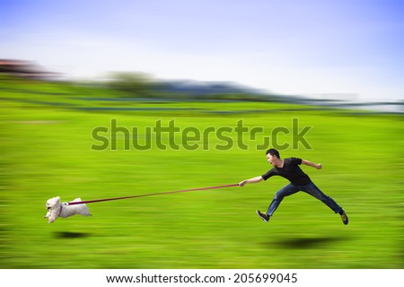 disobedient dog running fast and dragging a man by the leash - stock photo