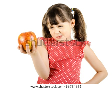 disobedient little girl hold apple and make displeased  grimace, on white background, isolated - stock photo