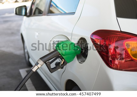 Dispenser pumping diesel or gasoline in car at gas station - stock photo