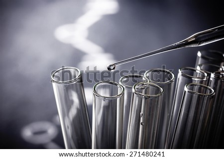 Dispensing water with pipette into tube. - stock photo