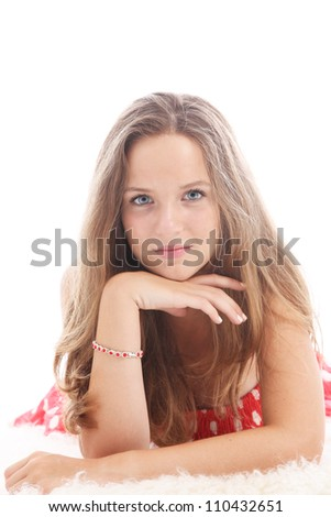 Dispirited teenage girl Dispirited teenage girl lying on a fluffy white carpet resting her chin on her hand with a withdrawn sad expression - stock photo