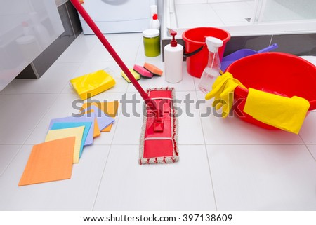 Display of assorted cleaning products on the clean white tiled floor in a bathroom with cloths, sponges, mop, bucket, basin and various chemicals and detergents - stock photo