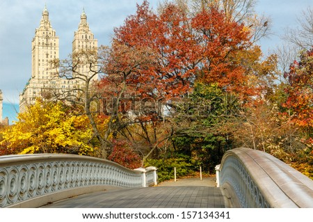 Display of autumn colors by the Bow Bridge in Central Park, with Upper West Side building behind the trees. New York. - stock photo