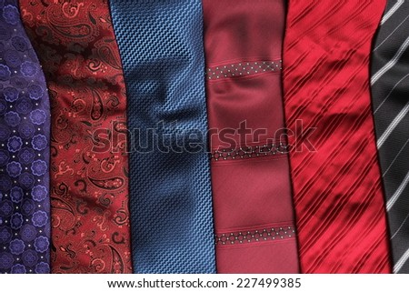 Display of classic and modern unrolled silk ties. Blue, purple, red, black and bordeaux - stock photo