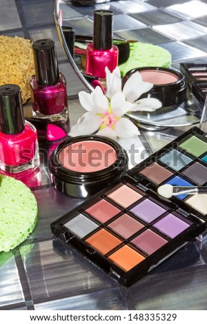 Display of colourful modern make up including eye shadow, nail varnish and blusher in front of a small portable cosmetics mirror - stock photo